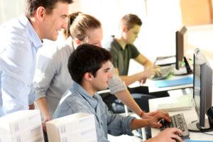 Students with teacher in front of desktop computer