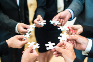 Teamwork - a group of eight business people assembling a jigsaw puzzle - representing team support and help concepts
